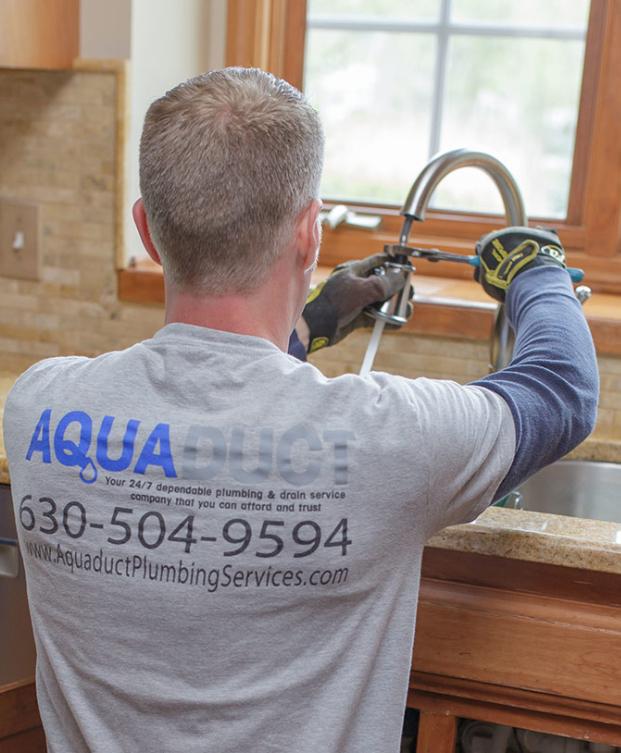 Plumber tightening kitchen faucet